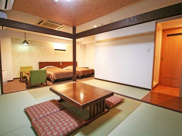 部屋に入ると手前に洋室ベッド二台、奥で一段上がって和室部分とバストイレ洗面と言う間取り