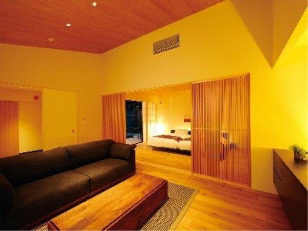 露天風呂付離れ(洋室)。リビングとベッドルームの2部屋に加えて露天風呂付き。木の質感を生かした室内。