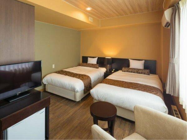 <ツインルーム>大きな窓から明かりの差し込むツインベッドの洋室。