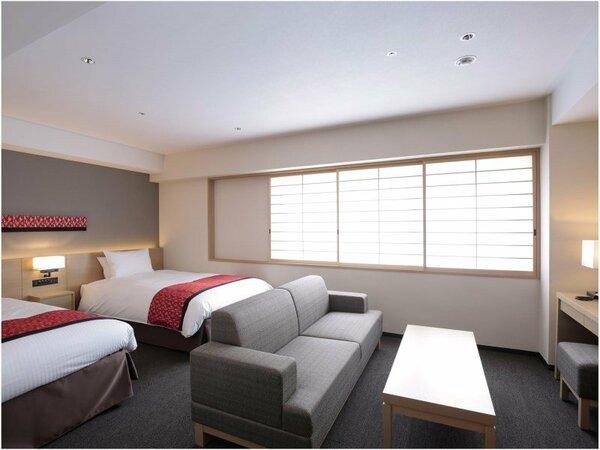 【デラックスツイン】35平米の室内は、ソファやティーテーブルを配した、ゆったりとお寛ぎいただける空間