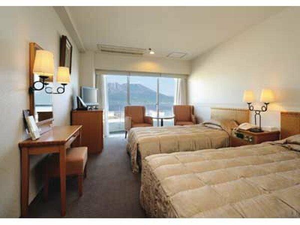 【ツインルーム・桜島側(22平米)】バルコニー付きの大きな窓から錦江湾越しに桜島をご覧いただけます。