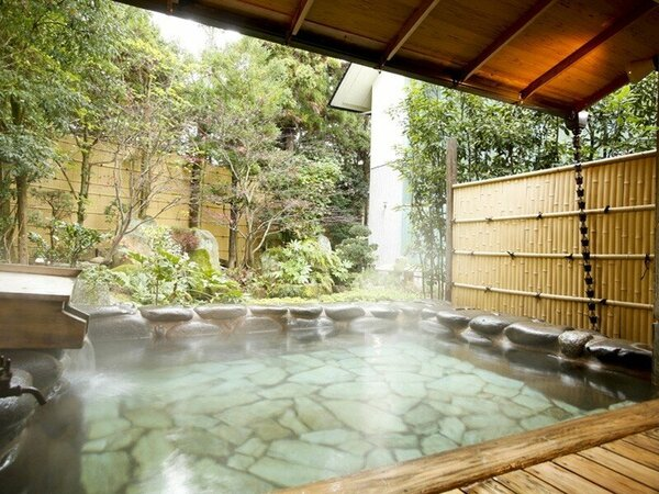 【男性大浴場:露天風呂】四季の草花に囲まれた開放的な岩風呂。