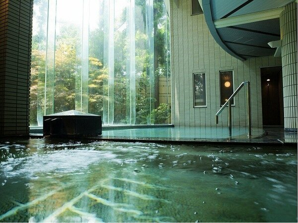 【温泉大浴場「月照の湯」:男性大浴場】ガラス張り吹き抜けの広々とした開放感のある温泉浴場です。