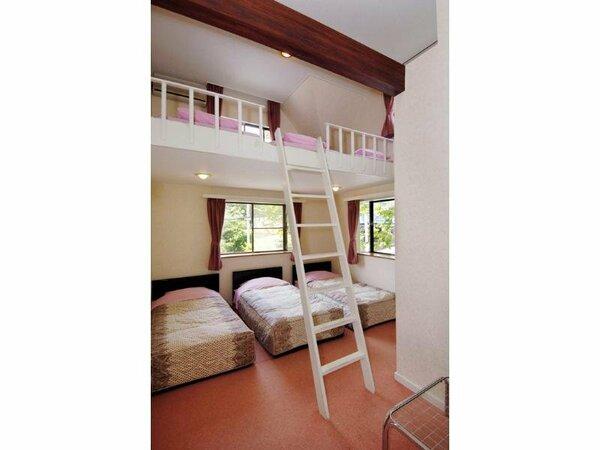 洋室にシングルベット3つ真ん中にハシゴがあり、ロフトにベットマット3つある6人用ロフトルームです。
