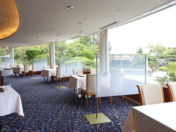 大きな窓からの景色が印象的なレストランです。席との距離を保てるようにパーティションを設置しています